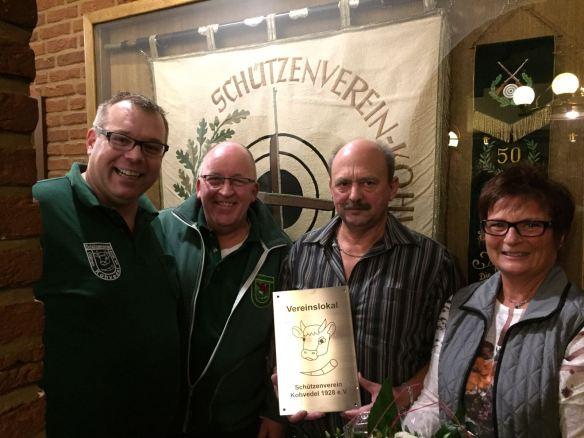 """Vor dem Fahnenschrank un mit dem Schild """"Vereinslokal"""" Oberst Björn, Vorsitzender Volker, Hansi und Elke Mölleck"""